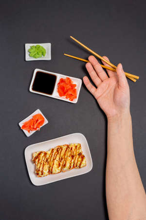 sushi, Maki rolls. On a plate on a black background with a space for your text. vertical photo, top view Фото со стока
