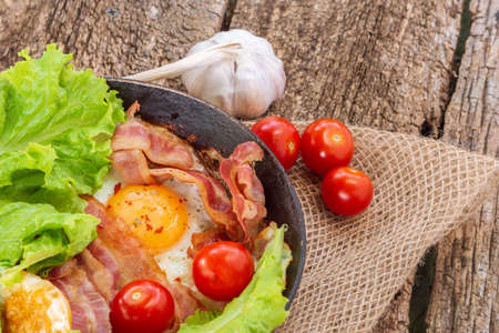 Pan of fried eggs with bacon, fresh tomatoes, salads, arugula. breakfast 免版税图像 - 151881927