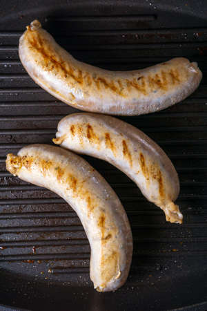 Grilled homemade sausages on iron grill frying pan. top view, flat lay