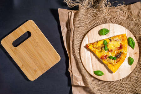 slice of pizza with Basil on a wooden Board. the view from the top lay flat. space for copying text