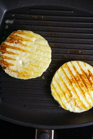 Grill Halloumi cheese in a frying pan. vertical photo 免版税图像