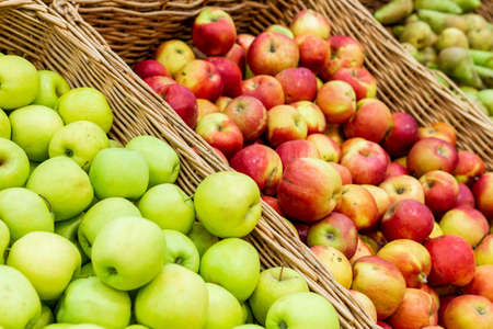 red, green apples on boxes in supermarket. Apples being sold at public market. Organic food 免版税图像