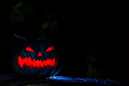 Scary smiling Halloween pumpkin on dark background. retro style, noise, selective focus 免版税图像 - 151858419