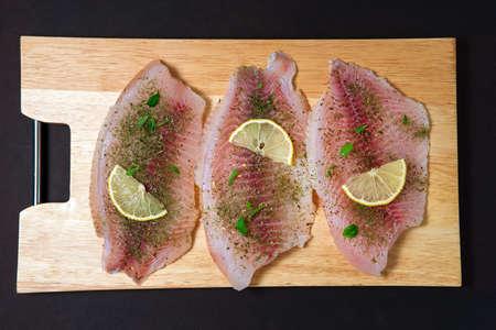Fresh raw fillet of tilapia fish with thyme, rosemary, lemon. food preparation 免版税图像 - 151881991