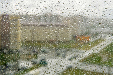 rain splashes fall on a window with a background. drop window a window pane with a blurred background 免版税图像 - 151857955