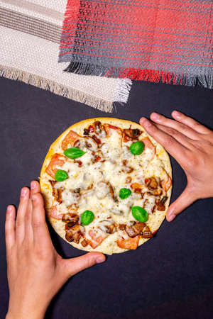 Pizza with mushrooms, ham, Basil and mozzarella cheese on black table. the view from the top, flat lay