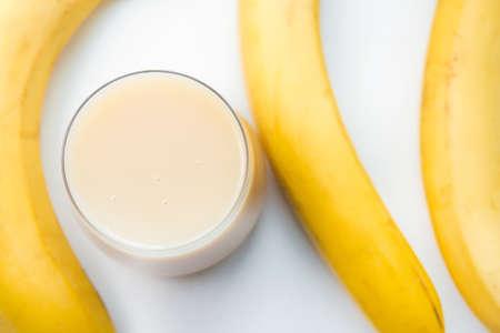 Banana smoothie, banana juice. Bananas on a gray light background, selective focus