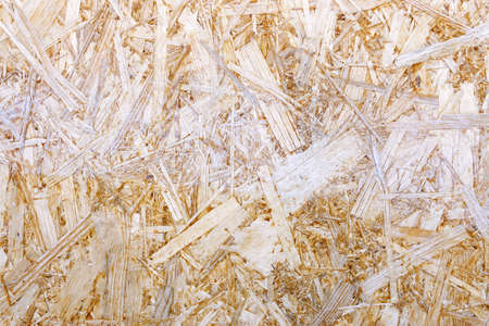 Construction materials made of chipboard. OSB wood panel made of pressed sand brown wood shavings as a close up background