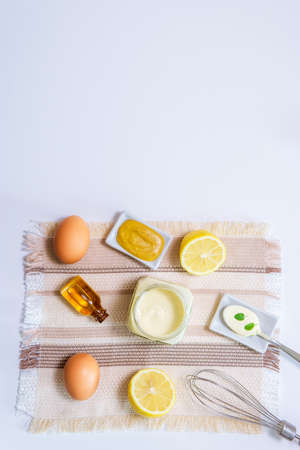 mayonnaise eg oil lemon mustard and wire whisk. top view copy space vertical photo