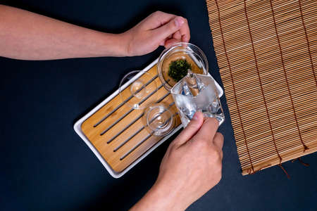 Japanese chinese tea teapot. hands pouring a hot drink, copy space background, top view flat lay Reklamní fotografie