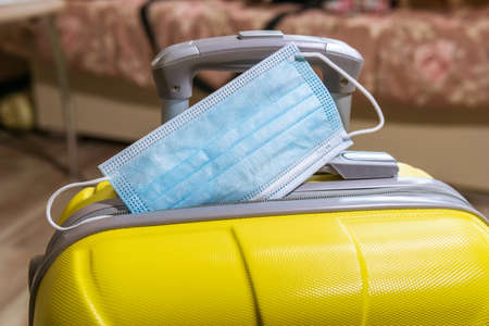 Suitcase with face mask. Preparing for trip abroad after corona virus pandemic. Travel concept.