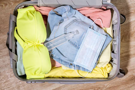 Top view of an open suitcase Packed with travel clothing. Conceptual background for travel and recreation. ncov-19 coronavirus pandemic 写真素材