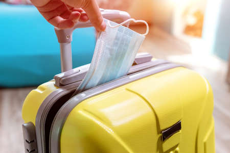 packing suitcase luggage including face mask and sanitizer to protect coronavirus covid-19, travel.