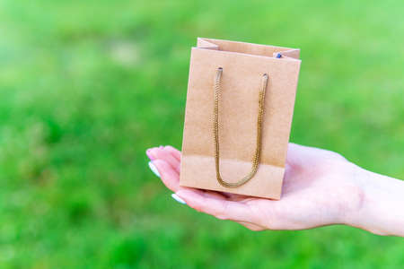 girl makes environmental purchases with paper bags in her hand. on a green natural background. to copy text. selective focus