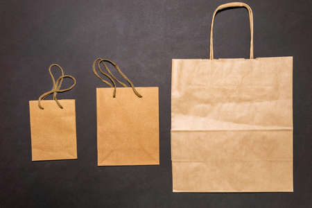 Eco paper bag with the inscription zero waste on black background, flat position, top view online shopping concept
