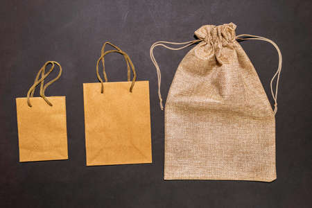 Eco concept. Cardboard boxes, paper bag on black background. Top view. Eco shopping concept, zero waste.
