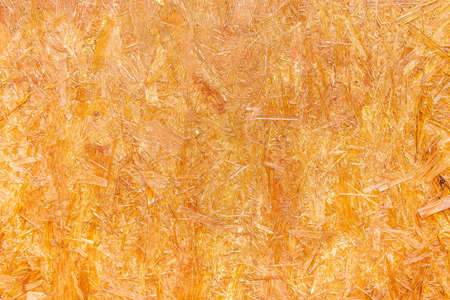 OSB are made of brown wood chips, ground into a wooden background. Top view of OSB wood veneer, dense, seamless surfaces.