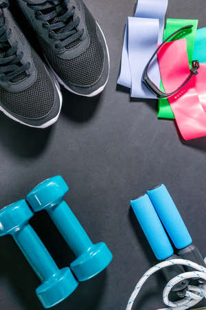 fitness sneakers, fitness bracelet, jump rope, dumbbells, elastic expander at the ankles. Lifestyle and health. flat lay. place to copy text