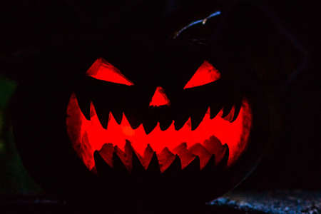 Scary smiling Halloween pumpkin on dark background. retro style, noise, selective focus
