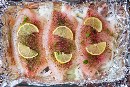 fillet of tilapia with spices and herbs, lemon and pepper on a cutting board top view