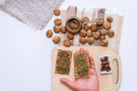 raw organic walnut butter or paste, fresh nuts on kitchen table. Top view