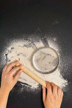 Male Baker sprinkle the dough with flour. The preparation of bread. The view from the top.