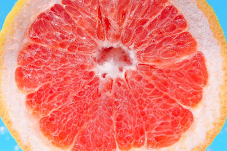red citrus- fruit slices of grapefruit. To close. ripe juicy fruit in water, under water, for juice 写真素材