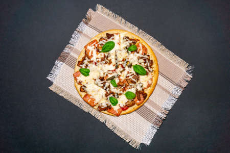 Pizza with Mozzarella cheese, Ham, Spices and Fresh Basil. Italian pizza.on black background. with copy space. top view. flat lay