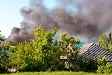 black smoke rises high into the sky. Fire outside the city.
