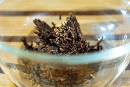 dry black tea in a glass bowl. Macro shot 免版税图像