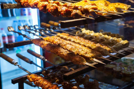 kababs are being grilled with heat in barbeque with metal skewers, at evening for sale as street food