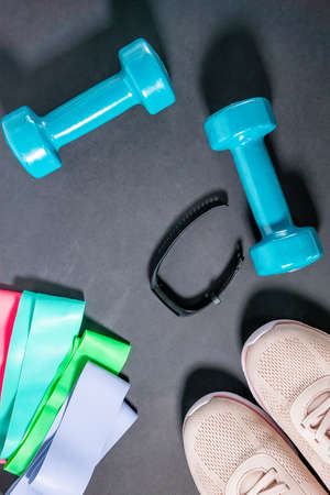 Fitness concept with sneakers, dumbbells, fitness bracelet, tracker, elastic expanders. Sports equipment on a black background. The concept of a healthy lifestyle