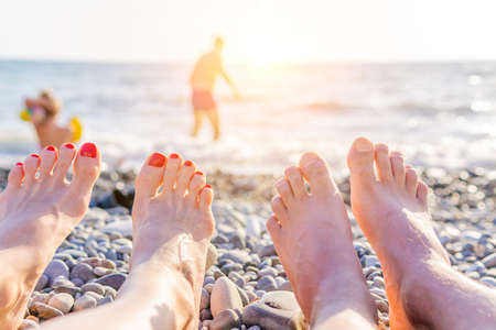 summer vacation at the sea, sunbathing vacation. legs of a man and a woman Imagens