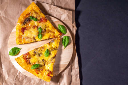 two slices of pizza with Basil on a wooden Board. top view flat lay. place to copy text