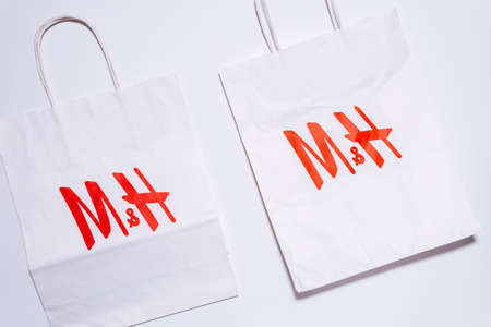 Tyumen, Russia-August 01, 2020: H and M logo on a white package top view. H and M Hennes Mauritz AB is a Swedish multinational retail-clothing company