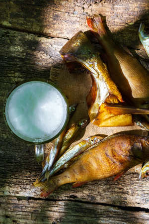 smoked fish perch, capelin on an old wooden table, top view Zdjęcie Seryjne