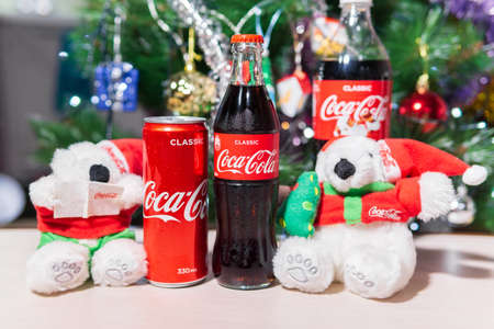 Tyumen, Russia-October 25, 2020: Bottle with coca cola at christmas background and white bear toys. 新闻类图片