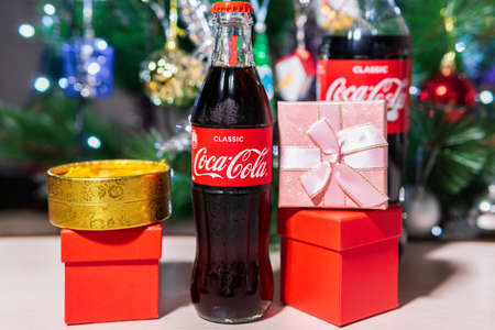Tyumen, Russia-October 25, 2020: Coca Cola in glass bottle. Christmas party drink. on the background of a Christmas tree selective focus 新闻类图片
