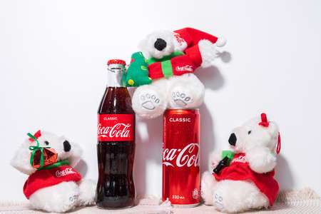 Tyumen, Russia-October 27, 2020: Coca Cola and white Christmas bears. on the background of a Christmas tree. selective focus 新闻类图片