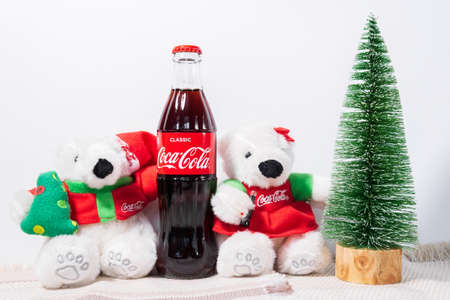 Tyumen, Russia-October 27, 2020: Coca Cola in glass bottle. Christmas party drink. on the background of a Christmas tree selective focus 新闻类图片