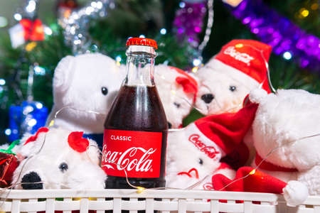 Tyumen, Russia-October 25, 2020: Coca Cola and white Christmas bears. on the background of a Christmas tree. selective focus