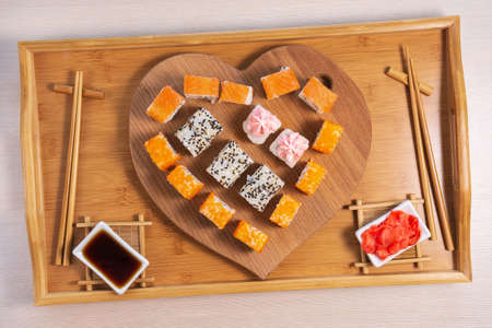 sushi rolls on a wooden background in the form of a heart. concept February 14, love Valentines day