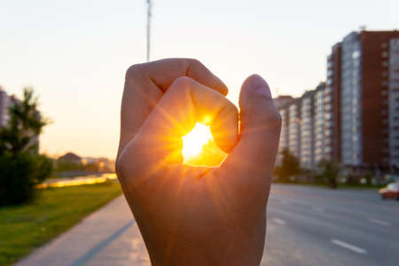 man hand on the background of the morning sunrise in the city, the urban landscape. selective focus