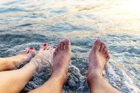 Vacation. legs close-up resting on the beach of the sea, enjoying the sun. travel concept 免版税图像