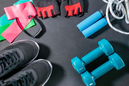 Lifestyle and health. fitness, sneakers, fitness bracelet, jump rope, dumbbells, elastic expander at the ankles. flat lay