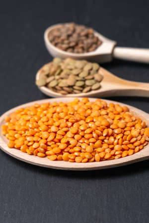 set consisting of different types lentils on a black background, top view. The concept of healthy and nutritious food