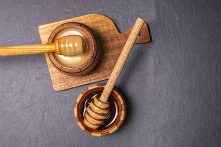 Natural honey with a spoon on a black rustic table. Top view flat lay 免版税图像