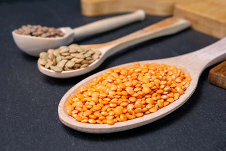 dry orange, red, green lentils in wooden spoons on a black background top view, flat lay