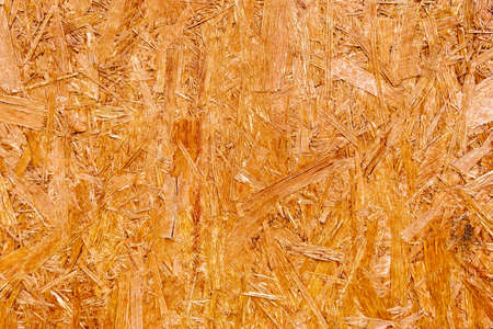 Wooden background.Textured wooden background made of pressed wood shavings of natural color. Фото со стока