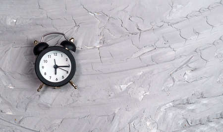 alarm clock on a gray concrete background. copy space. flat lay